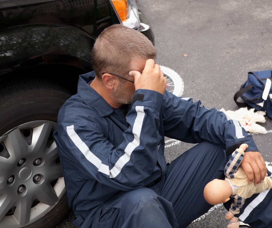first responder sitting on ground holding a child's doll at the scene of an accident